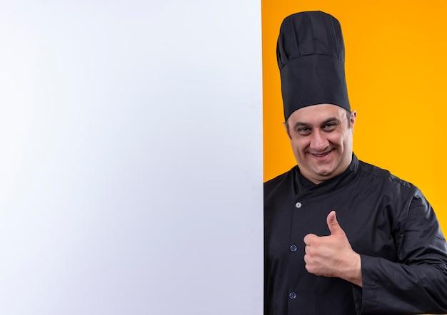 Cuoco maschio di mezza età sorridente in uniforme del cuoco unico che tiene la parete bianca il suo pollice su su fondo giallo con lo spazio della copia