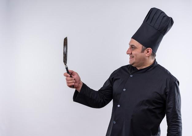 Cuoco maschio di mezza età sorridente in uniforme del cuoco unico che esamina la padella in sua mano con lo spazio della copia