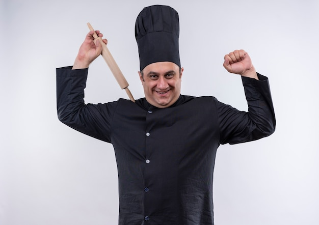 Smiling middle-aged male cook in chef uniform raising rolling pin showing strong gesture