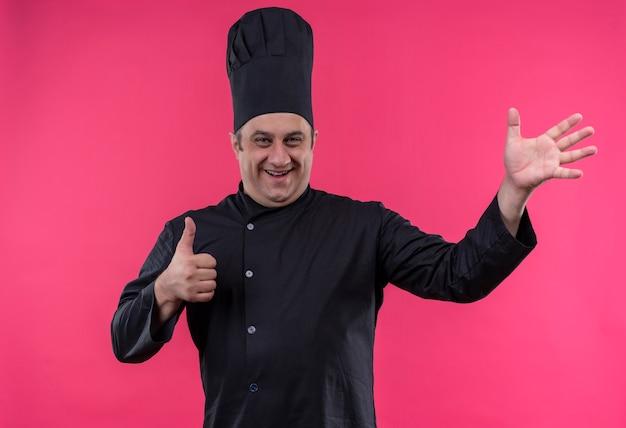 Cuoco maschio di mezza età sorridente in uniforme del cuoco unico che mostra i gesti differenti