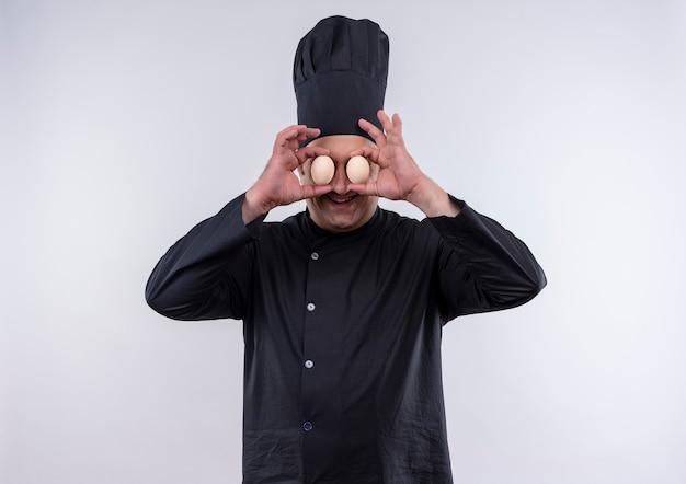 Sorridente cuoco maschio di mezza età in uniforme del cuoco unico che mostra il gesto di sguardo con le uova in mano