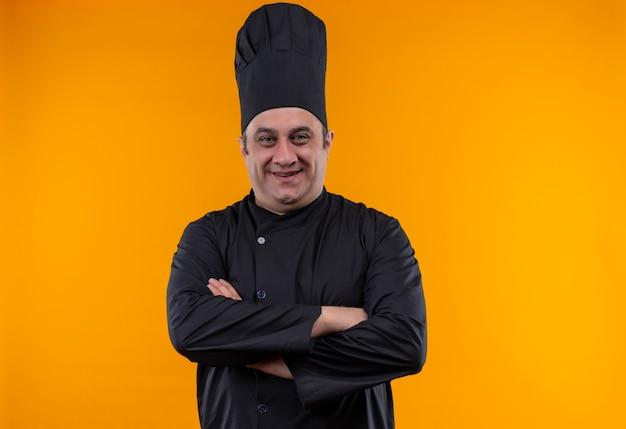 黄色の背景に手を交差させるシェフの制服を着た中年男性料理人の笑顔
