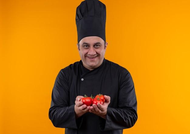黄色の背景にカメラにドメイトを差し出すシェフの制服を着た中年男性料理人の笑顔