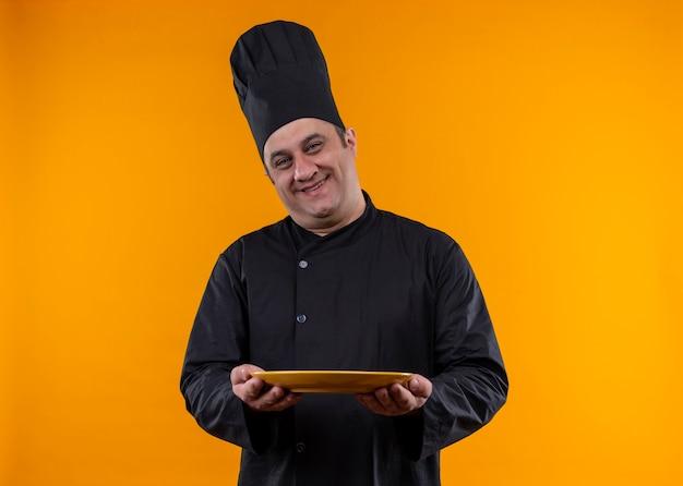 コピースペースと黄色の背景にプレートを保持しているシェフの制服を着た中年男性料理人の笑顔