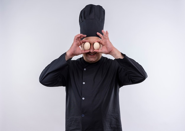 手に卵を持った表情のジェスチャーを示すシェフの制服を着た笑顔の中年男性料理人