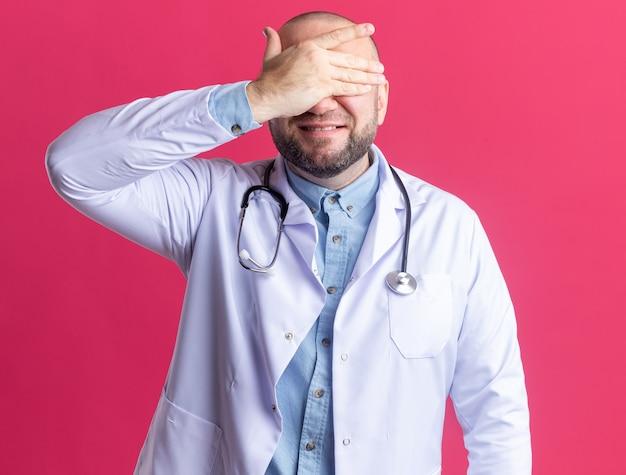 ピンクの壁に隔離された手で目を覆う医療ローブと聴診器を身に着けている中年男性医師の笑顔
