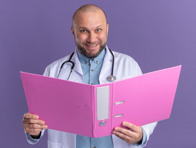 Smiling middle-aged male doctor wearing medical robe and stethoscope holding open folder  isolated on purple wall