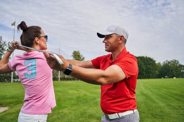 선글라스를 착용 한 여성에게 골프 기초를 가르치는 모자에 중년 남성 강사 미소 짓기