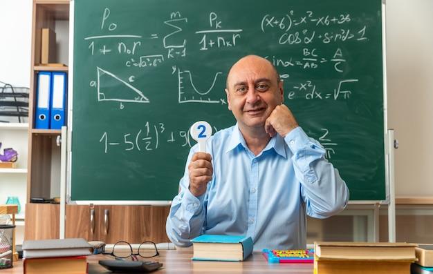 Sorridente insegnante maschio di mezza età si siede al tavolo con materiale scolastico tenendo il numero di fan in classe