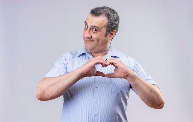 Smiling middle-aged man in blue vertical striped shirt showing heart sign with hands while standing on a white background