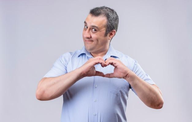 Uomo di mezza età sorridente in camicia a strisce verticali blu che mostra il segno del cuore con le mani mentre levandosi in piedi su una priorità bassa bianca