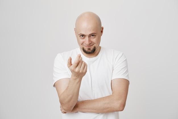 Улыбающийся мужчина средних лет показывает жест, приманка