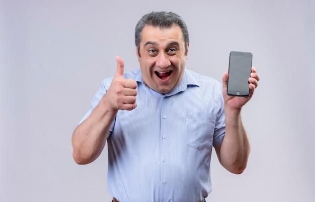 携帯電話を押しながら白い背景の上に立っている間親指を現して青いシャツを着て中年の男の笑顔