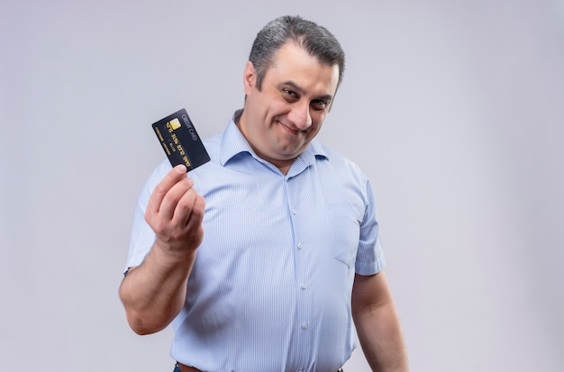 Smiling middle-aged man wearing blue vertical striped shirt holding credit card while standing on a white background