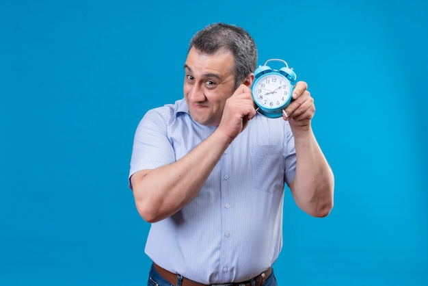 Smiling middle-aged man wearing blue vertical striped shirt listening to clock ticking sound holding blue alarm clock on a blue background