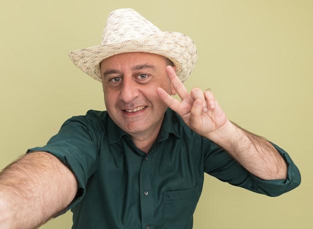 올리브 녹색 벽에 고립 된 평화 제스처를 보여주는 녹색 티셔츠와 모자를 쓰고 웃는 중년 남자
