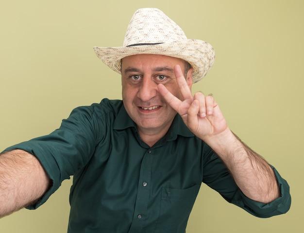 Sorridente uomo di mezza età che indossa t-shirt verde e cappello tenendo la parte anteriore che mostra gesto di pace isolato sulla parete verde oliva