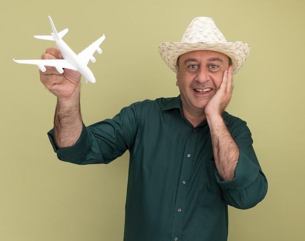 Sorridente uomo di mezza età che indossa t-shirt verde e cappello che tiene aeroplano giocattolo mettendo la mano sul mento isolato sulla parete verde oliva