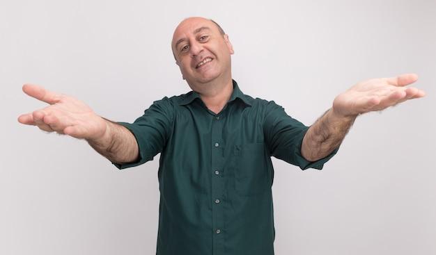白い壁に隔離されたカメラで手を差し伸べる緑のtシャツを着て笑顔の中年男性