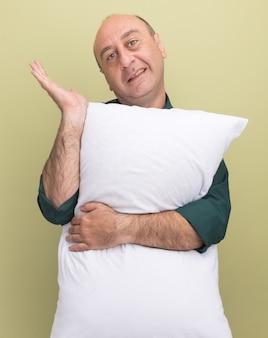 Sorridente uomo di mezza età che indossa la maglietta verde abbracciò i punti del cuscino con la mano sul lato isolato sulla parete verde oliva