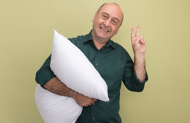 Sorridente uomo di mezza età che indossa la maglietta verde abbracciò il cuscino che mostra la pace isolata sulla parete verde oliva
