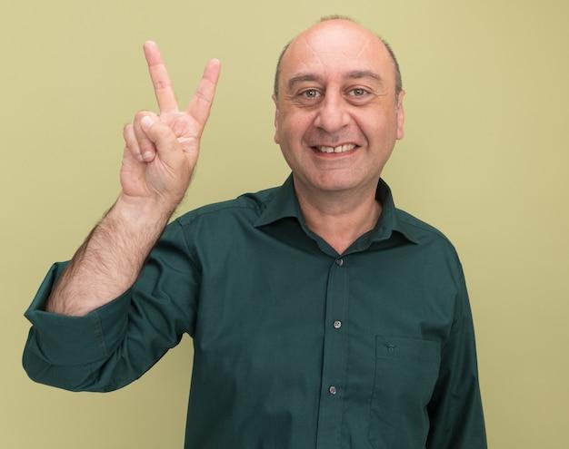 Uomo di mezza età sorridente che indossa la maglietta verde che mostra gesto di pace isolato sulla parete verde oliva