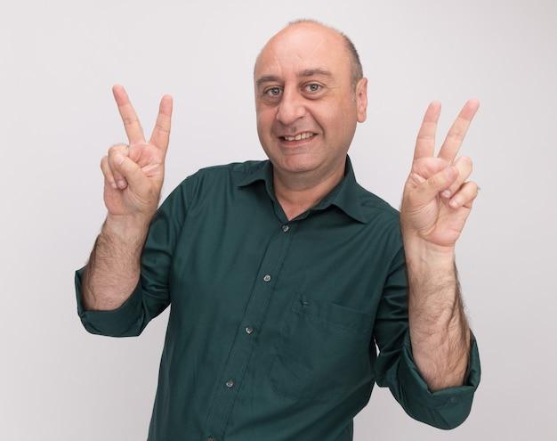 흰 벽에 고립 된 평화 제스처를 보여주는 녹색 티셔츠를 입고 웃는 중년 남자