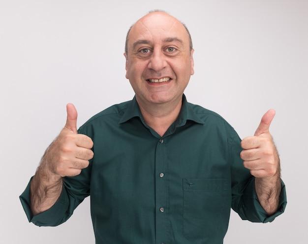 흰 벽에 고립 된 엄지 손가락을 보여주는 녹색 티셔츠를 입고 웃는 중년 남자