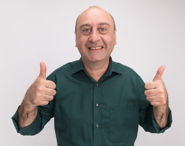 Smiling middle-aged man wearing green t-shirt showing thumbs up isolated on white wall