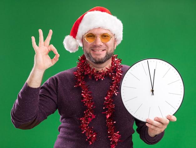 Улыбающийся мужчина средних лет в шляпе санта-клауса и гирлянде из мишуры на шее в очках с часами, держащими часы и делающий знак ок, изолированный на зеленой стене
