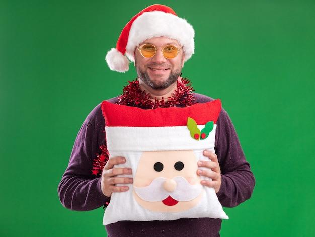 Улыбающийся мужчина средних лет в шляпе санта-клауса и гирлянде из мишуры на шее в очках держит подушку санта-клауса, изолированную на зеленой стене