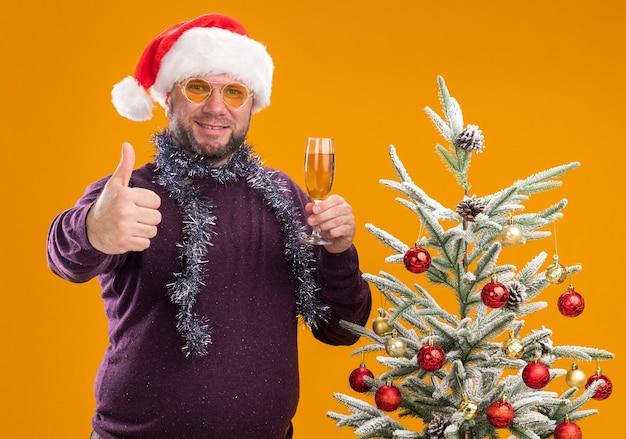 Uomo di mezza età sorridente che porta il cappello della santa e la ghirlanda della canutiglia intorno al collo con gli occhiali che stanno vicino all'albero di natale decorato che tiene vetro di champagne