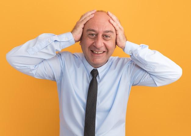 Улыбающийся мужчина средних лет в белой футболке с галстуком схватил голову на оранжевой стене