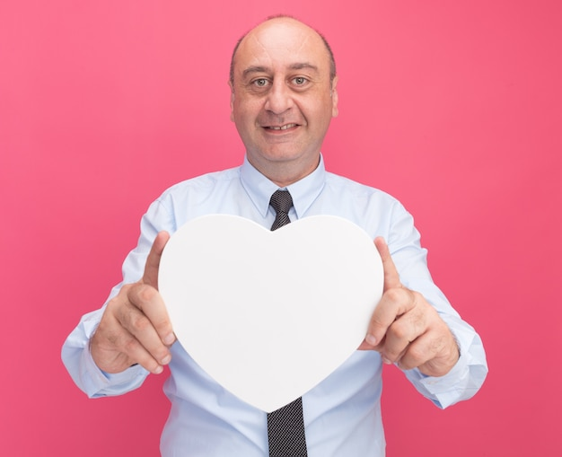 Улыбающийся мужчина средних лет в белой футболке с галстуком, протягивая коробку в форме сердца перед камерой, изолированной на розовой стене