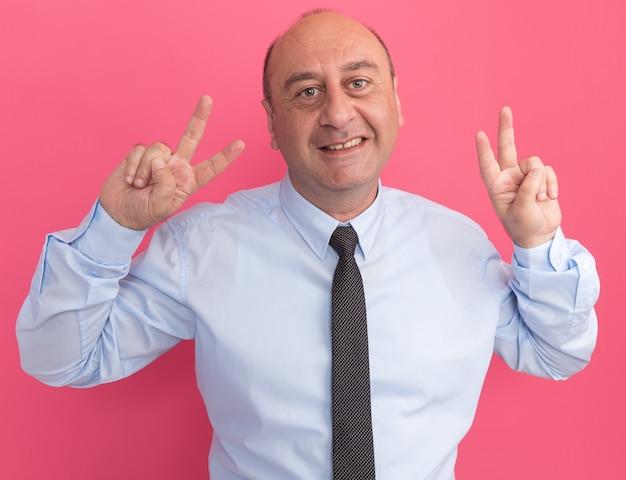 Sorridente uomo di mezza età che indossa la maglietta bianca con cravatta che mostra gesto di pace isolato sulla parete rosa