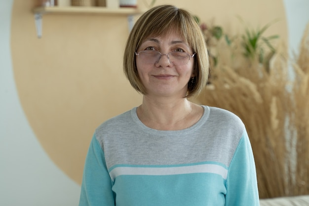 Smiling middle aged mature woman looking at front having confident happy facial expression