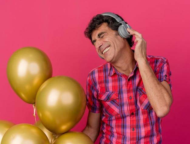 Улыбающийся мужчина средних лет в наушниках держит воздушные шары и слушает музыку с закрытыми глазами, изолированными на розовой стене