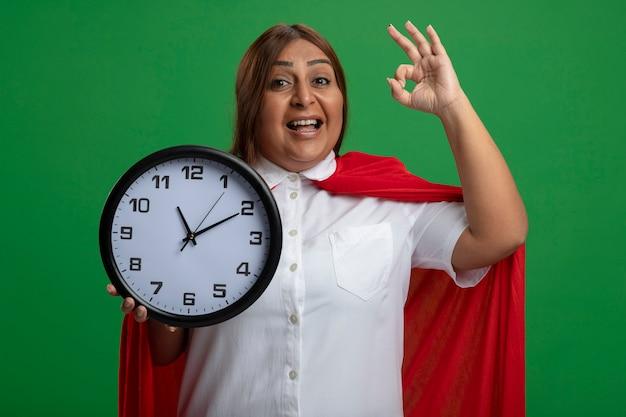 Улыбающаяся женщина супергероя средних лет держит настенные часы и показывает нормальный жест, изолированные на зеленом фоне