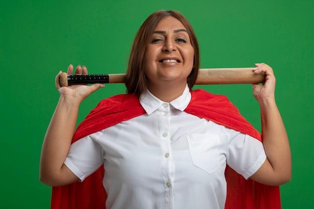Smiling middle-aged superhero female putting baseball bat behind neck isolated on green background