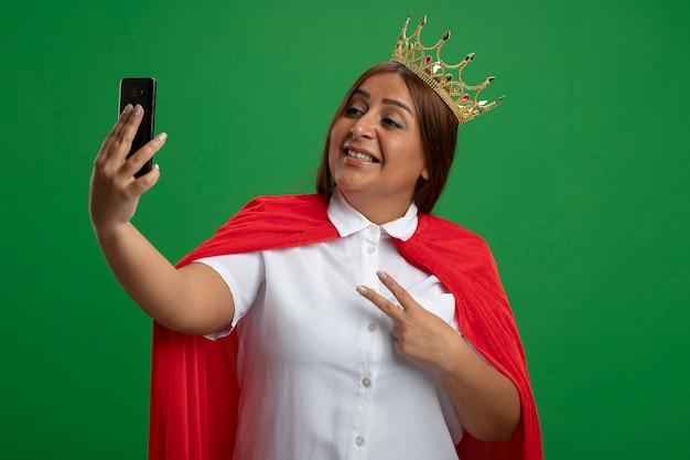 왕관을 쓰고 웃는 중년 슈퍼 히어로 여성이 녹색 배경에 고립 된 평화 제스처를 보여주는 셀카를 가져 가라.