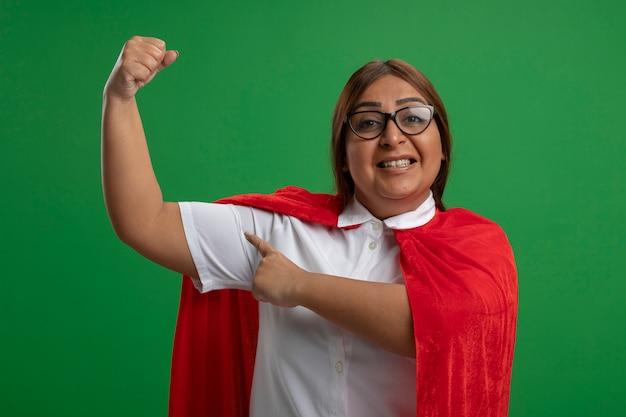 緑に分離された強いジェスチャーを示す眼鏡をかけている中年のスーパーヒーローの女性の笑顔