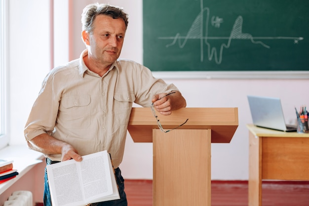 Smiling middle aged teacher holding a book standing and leaning to tribune.