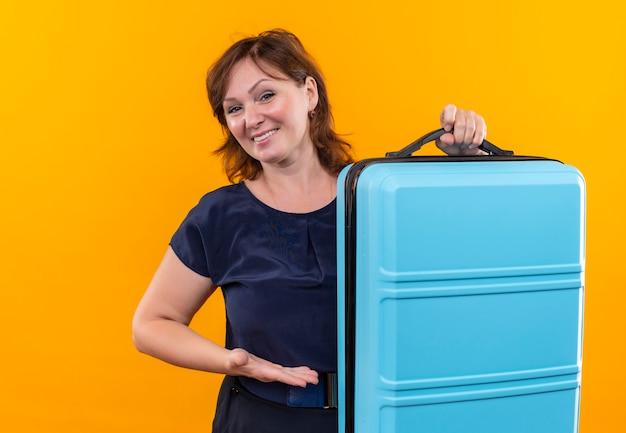 Улыбающаяся женщина-путешественница средних лет держит и указывает на чемодан на изолированной желтой стене