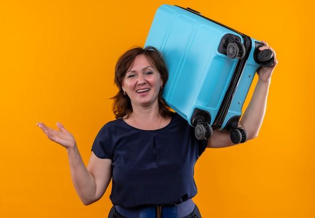 Улыбающаяся женщина-путешественница средних лет держит чемодан на плече и протягивает руку на изолированной желтой стене