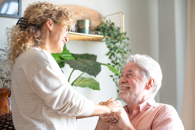 Улыбающаяся женщина средних лет и старший отец проводят время вместе дома