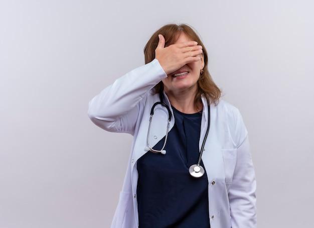 医療ローブと聴診器を身に着けている中年女性医師を笑顔でコピースペースと孤立した白い壁に手で目を閉じて