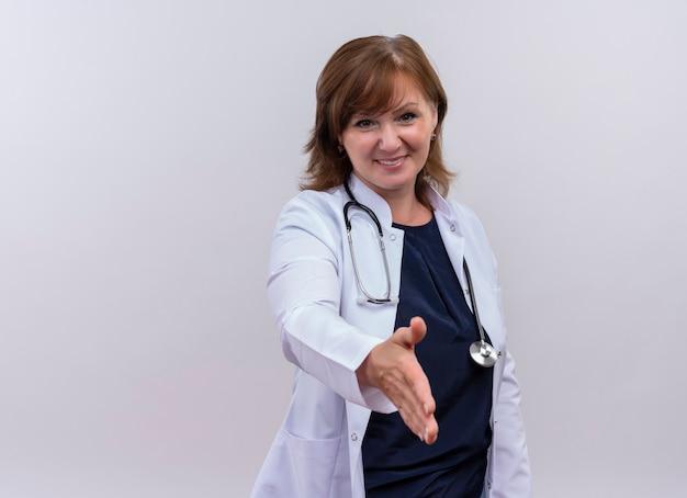 Улыбающаяся женщина-врач средних лет в медицинском халате и стетоскопе делает жест рукопожатия на изолированной белой стене с копией пространства