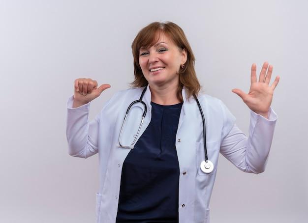 医療ローブと自分で指で指している聴診器を着て、孤立した白い壁に5つを示す中年女性医師の笑顔