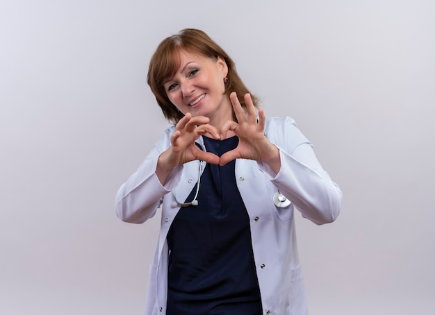 Sorridente donna di mezza età medico indossando abito medico e stetoscopio facendo segno di cuore sulla parete bianca isolata con lo spazio della copia