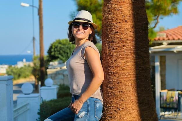 열 대 해변 휴양지에서 휴가를 즐기는 중년 여성, 황금 시간에 일몰 미소. 공간 복사